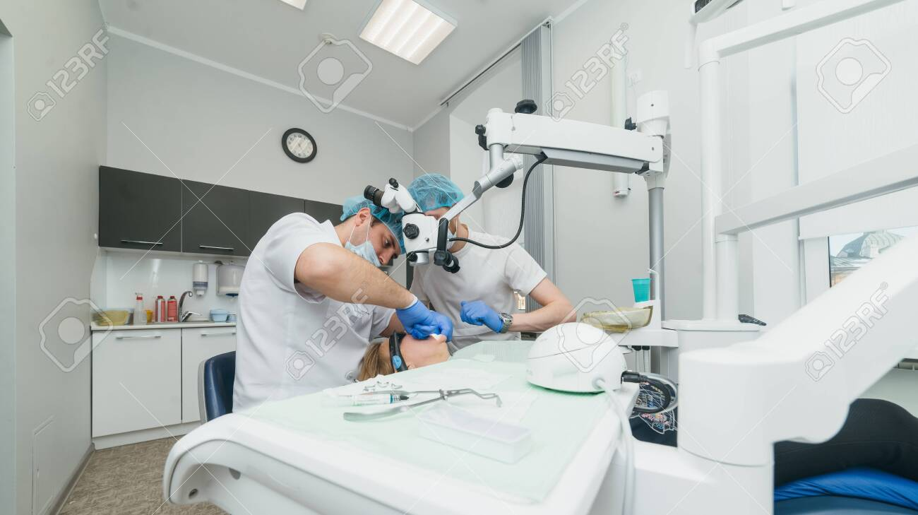 Doctor used microscope. Dentist is treating patient in modern dental office. Operation is carried out using cofferdam. Client is inserted and restored teeth, make denture. Orthodontist and assistant work in protective masks. - 135511908