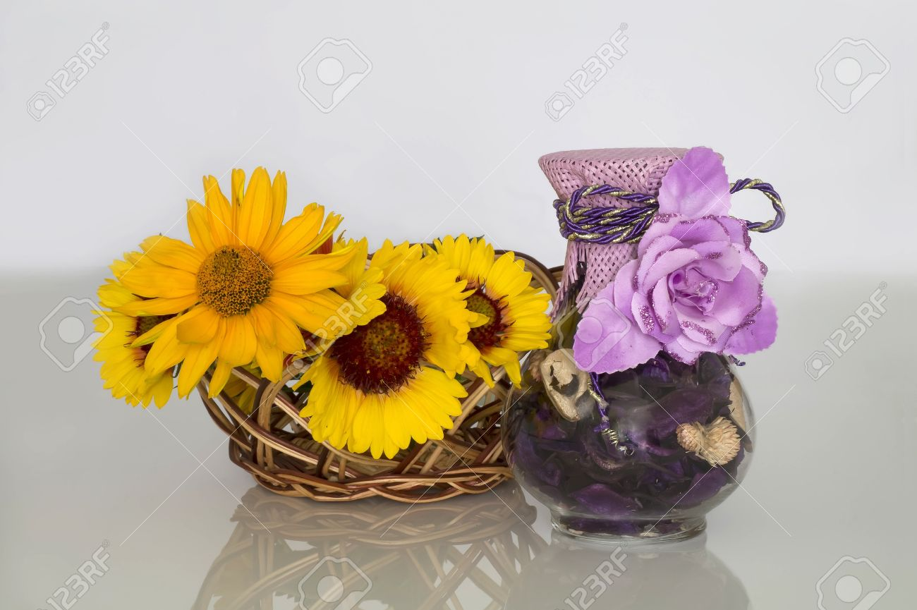 On A Grey Smooth Table Yellow Flowers In A Basket From A Rod Stock