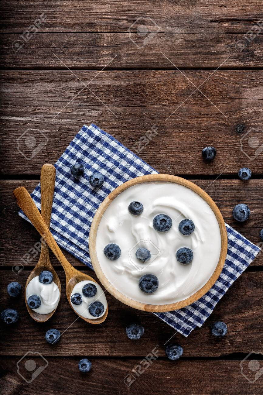 blueberry yogurt in a bowl on wooden table top view - 61699443