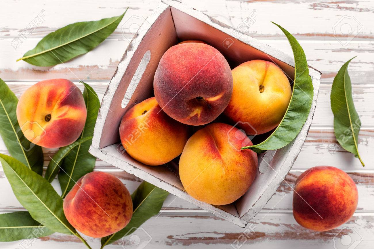 fresh peaches with leaves on white wooden table top view - 61699454
