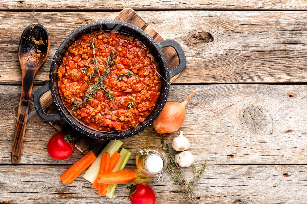 classic italian bolognese sauce stewed in cauldron with ingredients on wooden table, top view, culinary background with space for text - 97027682