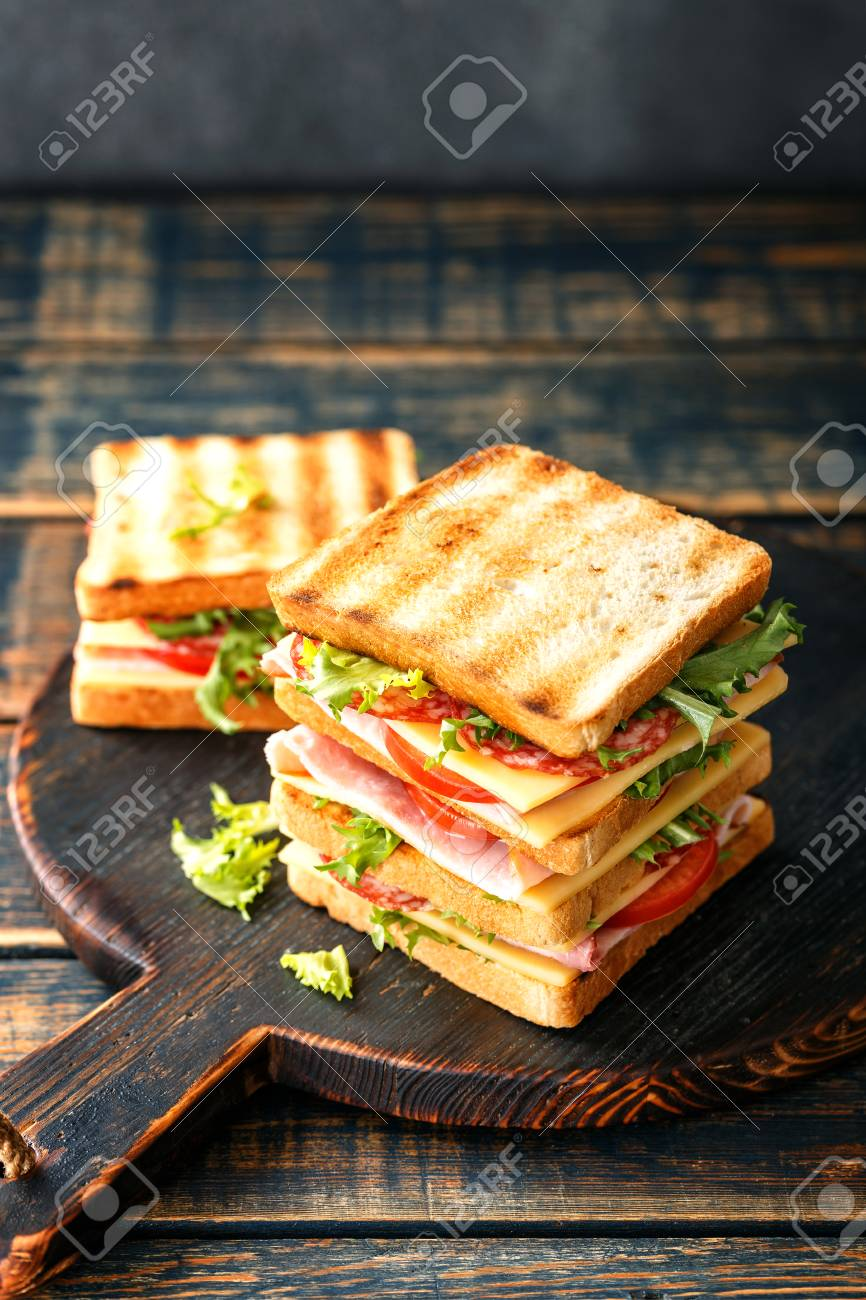 sandwiches with grilled toast ham salami cheese tomatoes and lettuce - 113696987