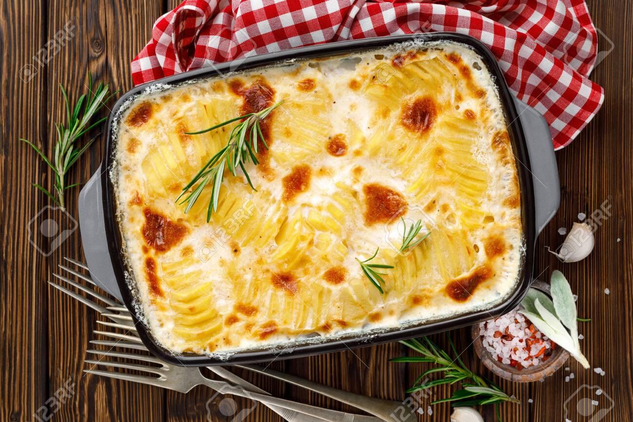 Potato gratin. Baked potato with cream, cheese and garlic - 129759846