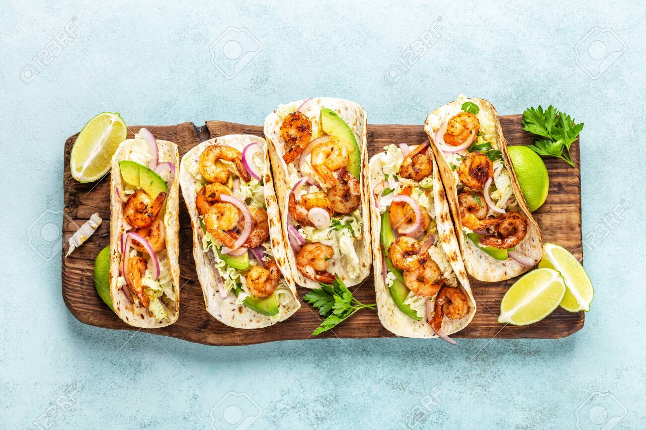 Shrimp tacos. Seafood fajitas with cabbage, onion, parsley in tortillas served on wooden cutting board - 129760646
