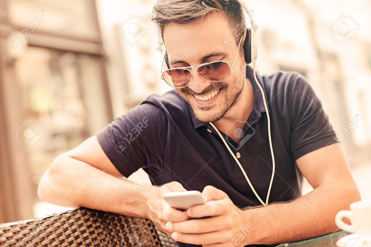 young man listening to music on a smart phone he is listening