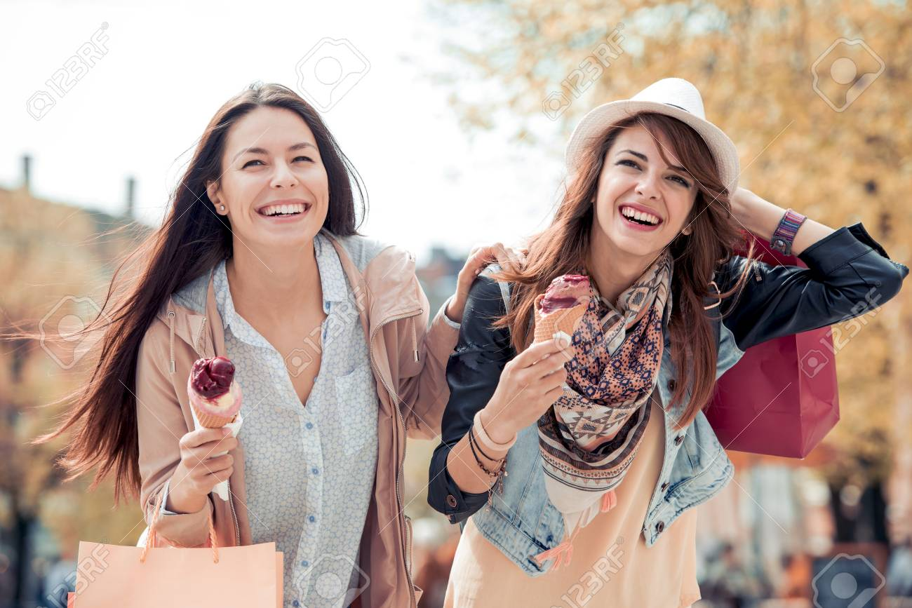 9bb5dc879a Stock Photo - Two young female friends having fun and eating ice cream.  Cheerful young women eating icecream outdoors.