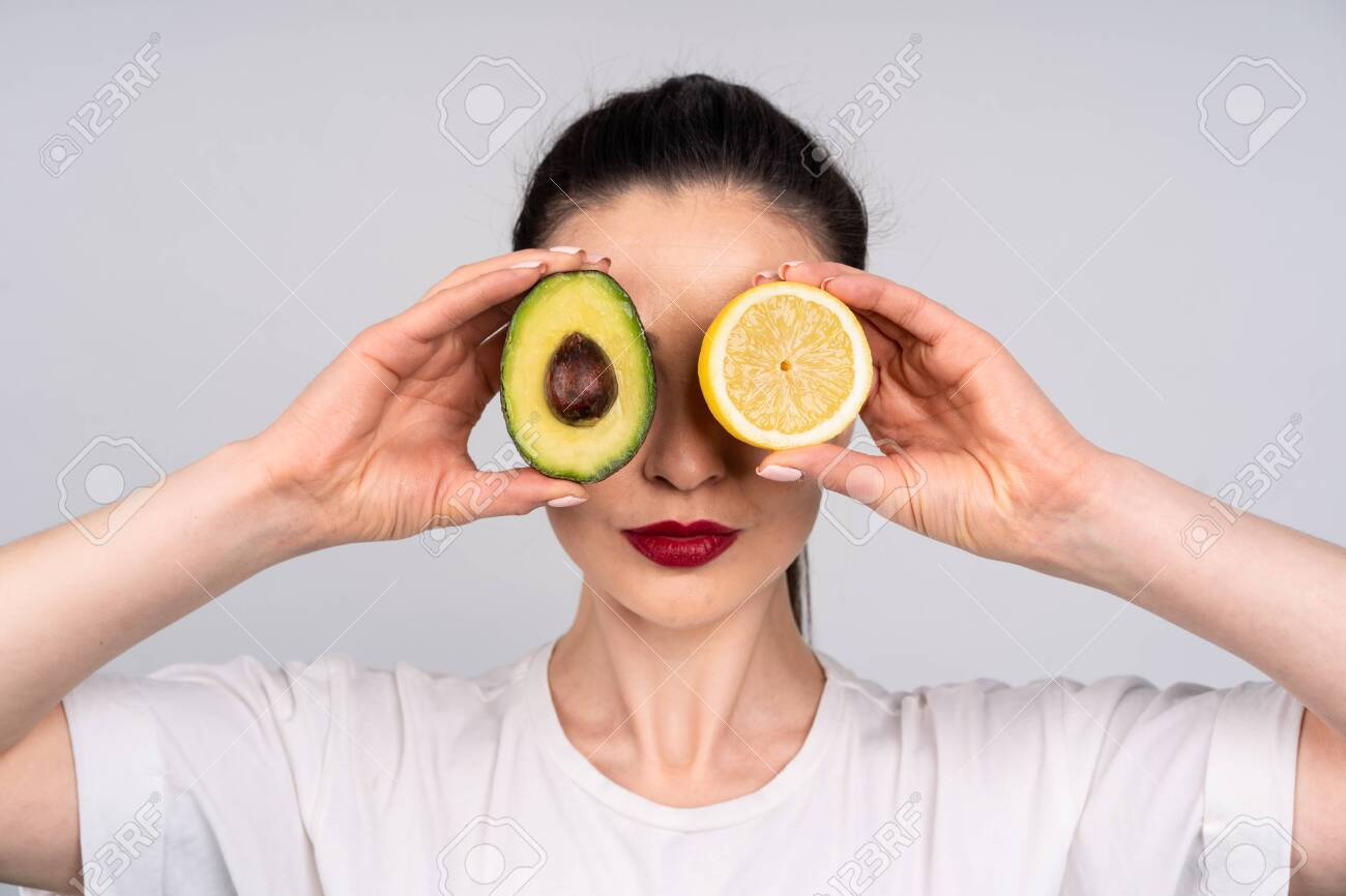 Girl in white shirt holds the halves of the avocado and orange right next to the eye, the concept of beauty and health - 149473378