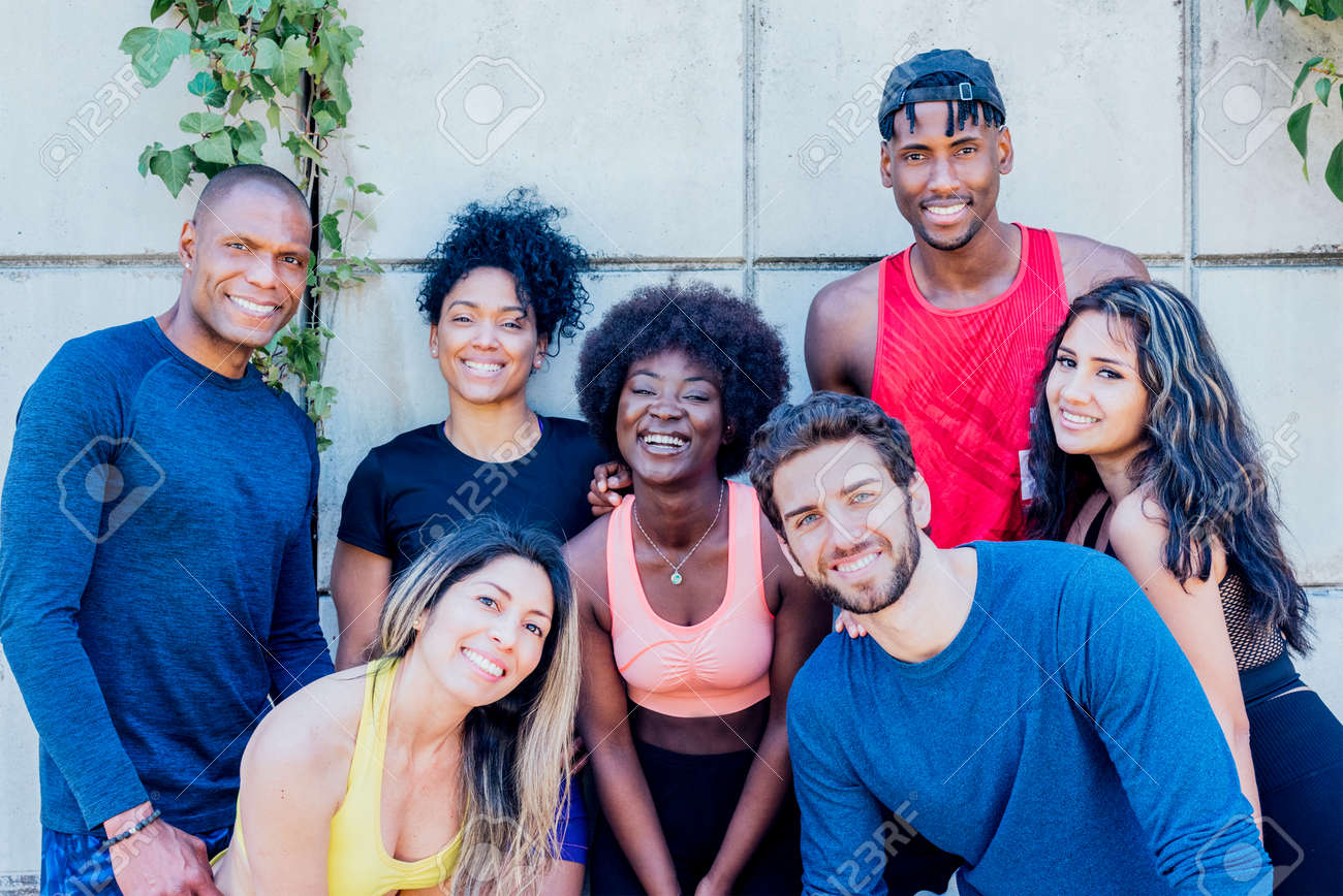 Portrait of a group of runners smiling at camera. - 169297942