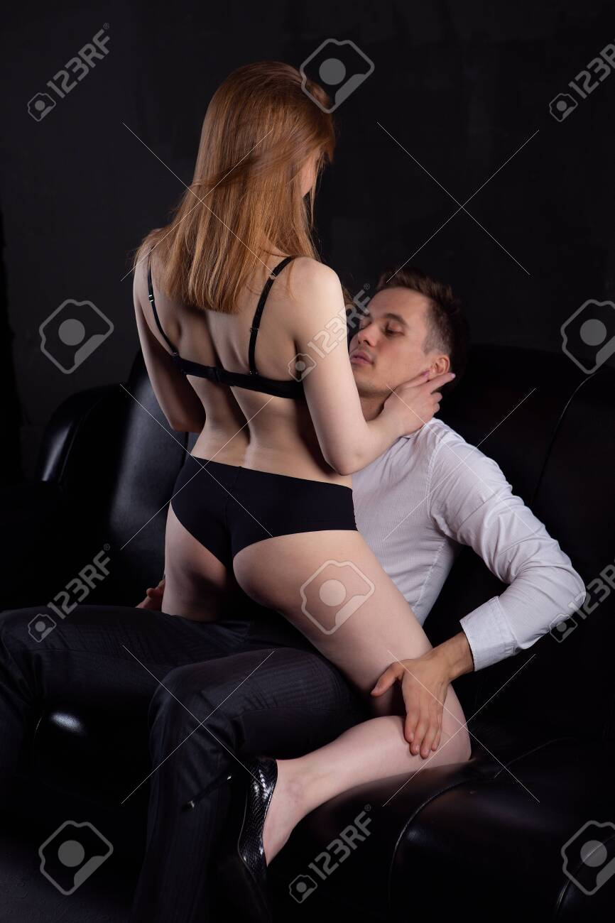 Sexy young couple. Undressed sensual blonde woman with a beautiful body in black underwear sits on a muscular man, kissing undressing him in the room on a dark background. Studio vertical photography - 150660635