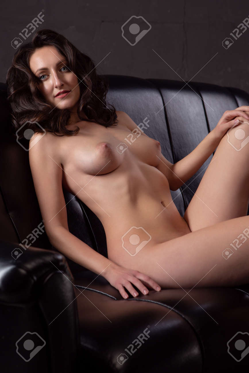 Gorgeous young brunette woman lies on a black leather sofa - 165306112