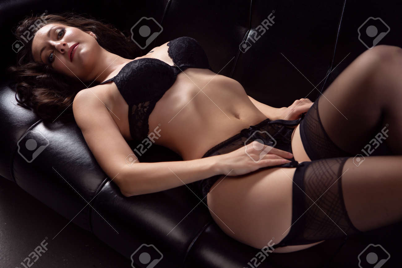 Portrait of a young brunette woman posing in lace underwear on a black leather sofa - 165334765