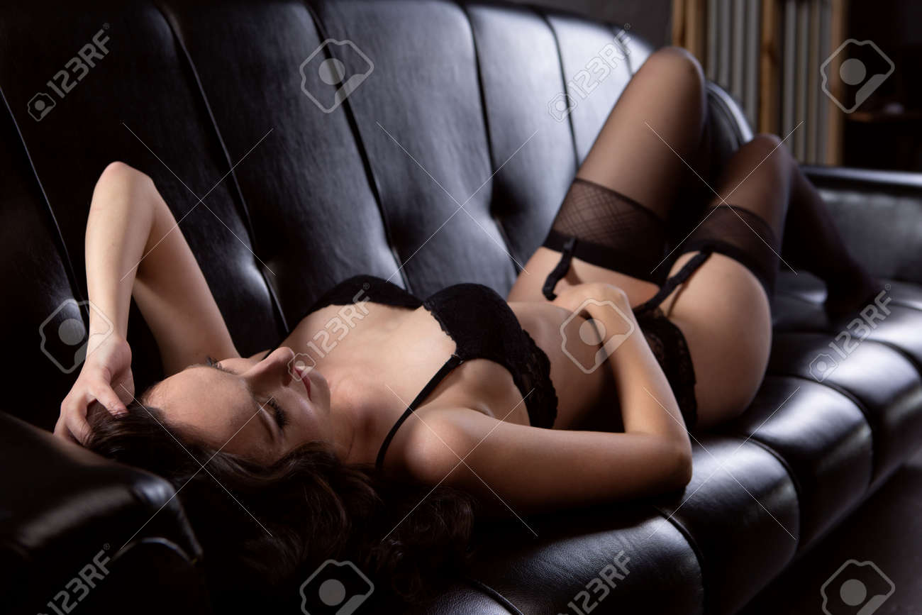 Gorgeous young woman in black underwear lies on the sofa - 167273884