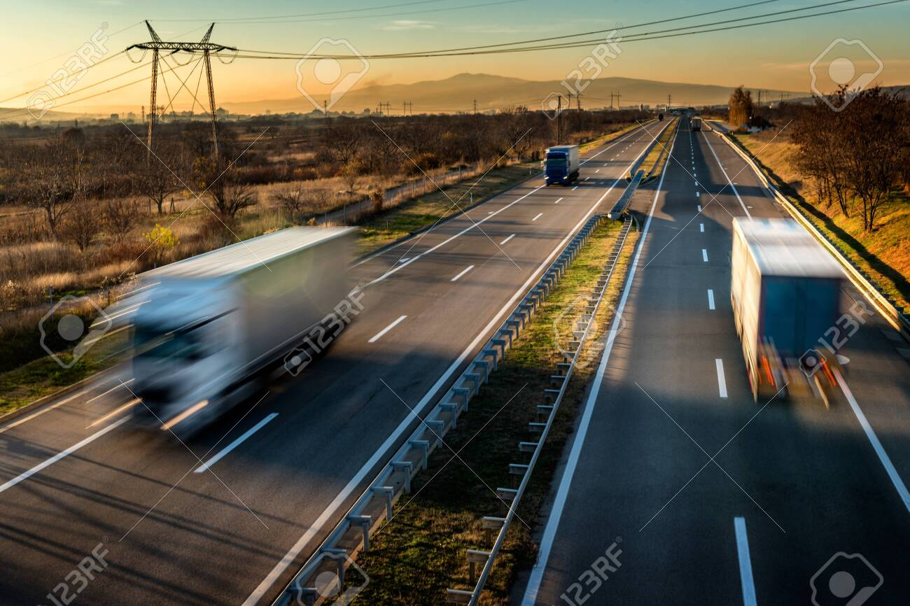 Delivery trucks in high speed driving on a highway through rural landscape. Fast blurred motion drive on the freeway. Freight scene on the motorway - 137407864