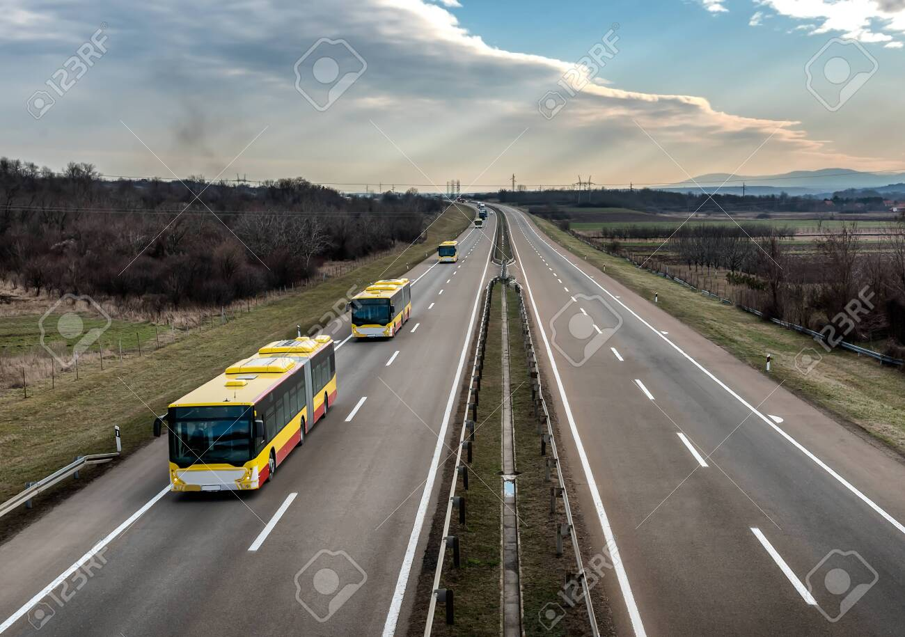 Intercity Yellow Line Buses in line traveling on a rural country highway. Bus passenger transportation concept. - 147725989
