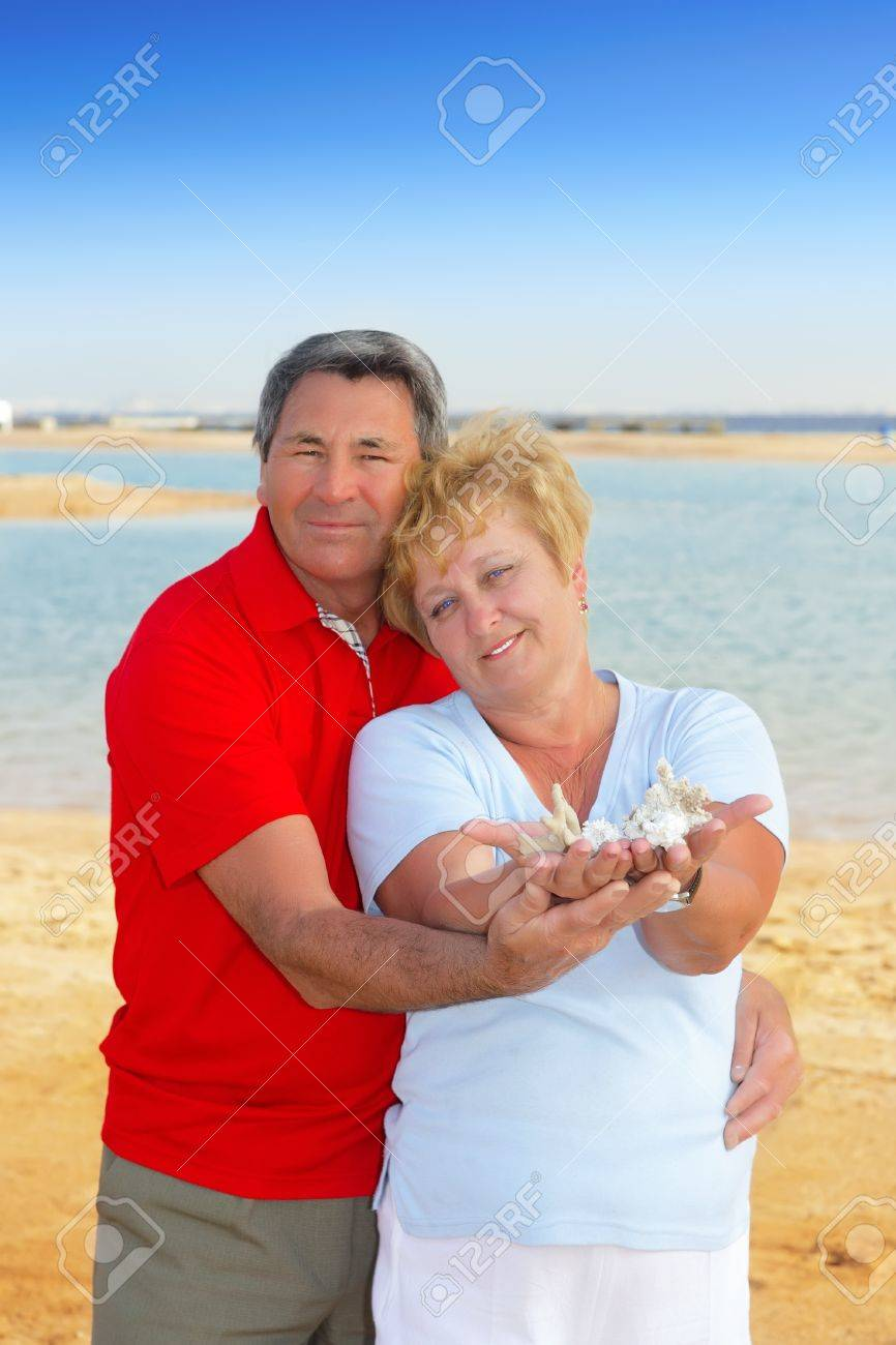Elderly couple on the coast , holding seashells and corals in his arms. Stock Photo - 10275775