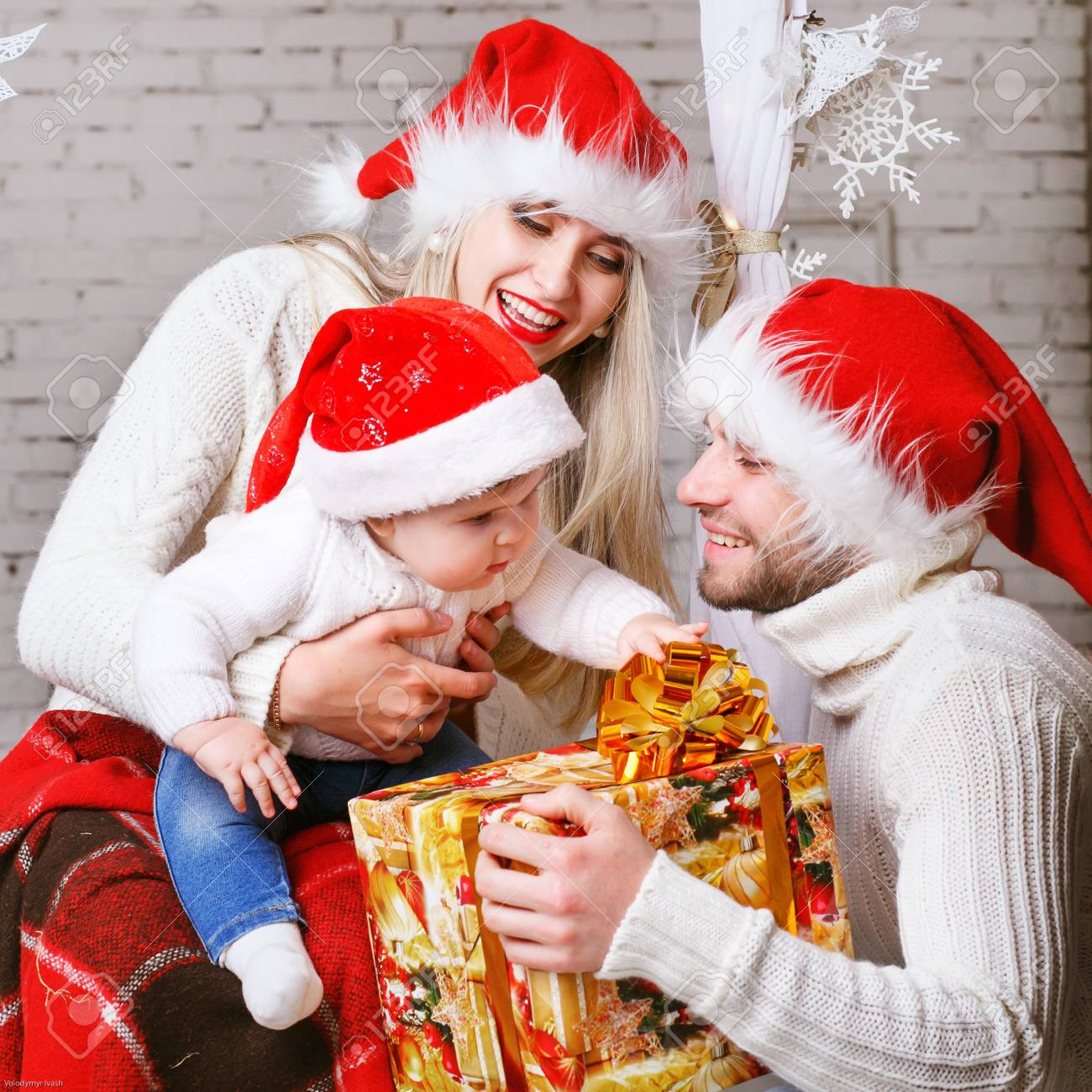 Young Family In White Sweaters And Red Hats Gifts Share New Years