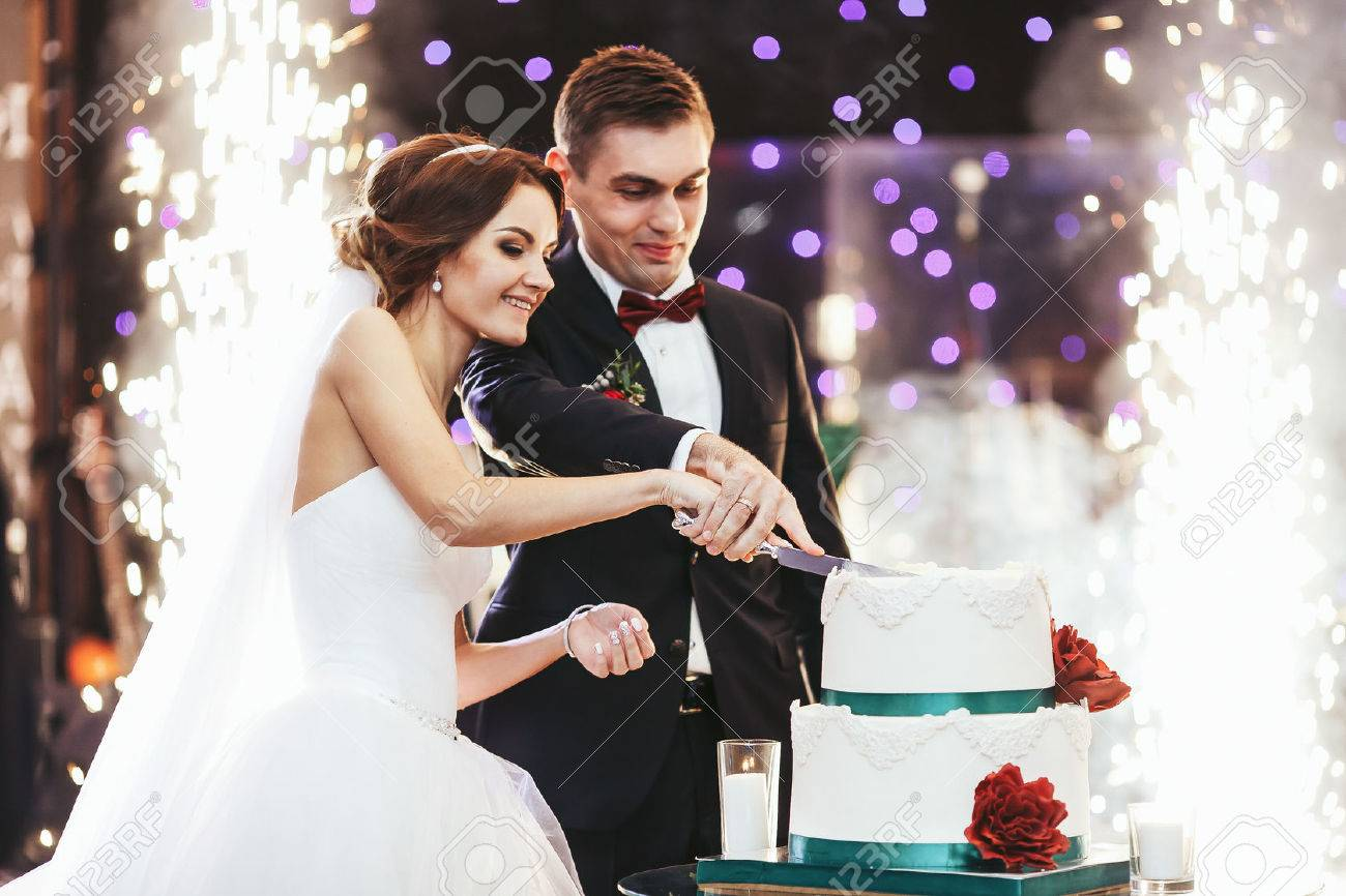 Happy bride and groom cut the wedding cake in the front of fireworks - 64223820