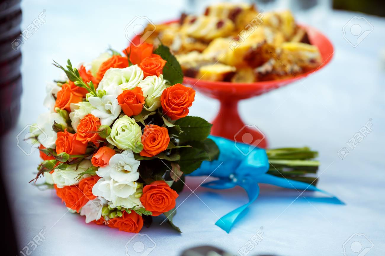 A Wedding Bouquet Of Orange And White Roses Lies On A Table Stock