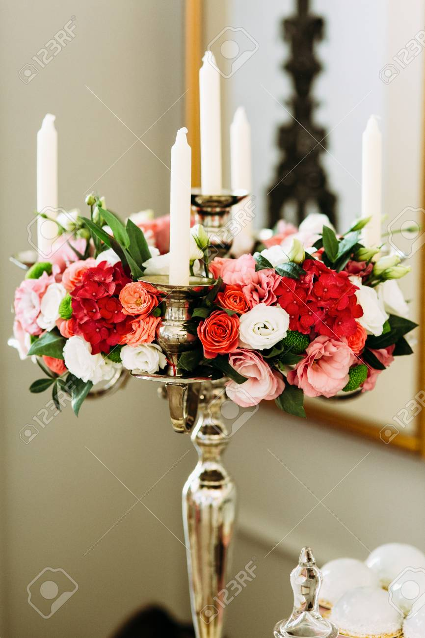 Stock Photo - White candles and bouquet of colorful flowers
