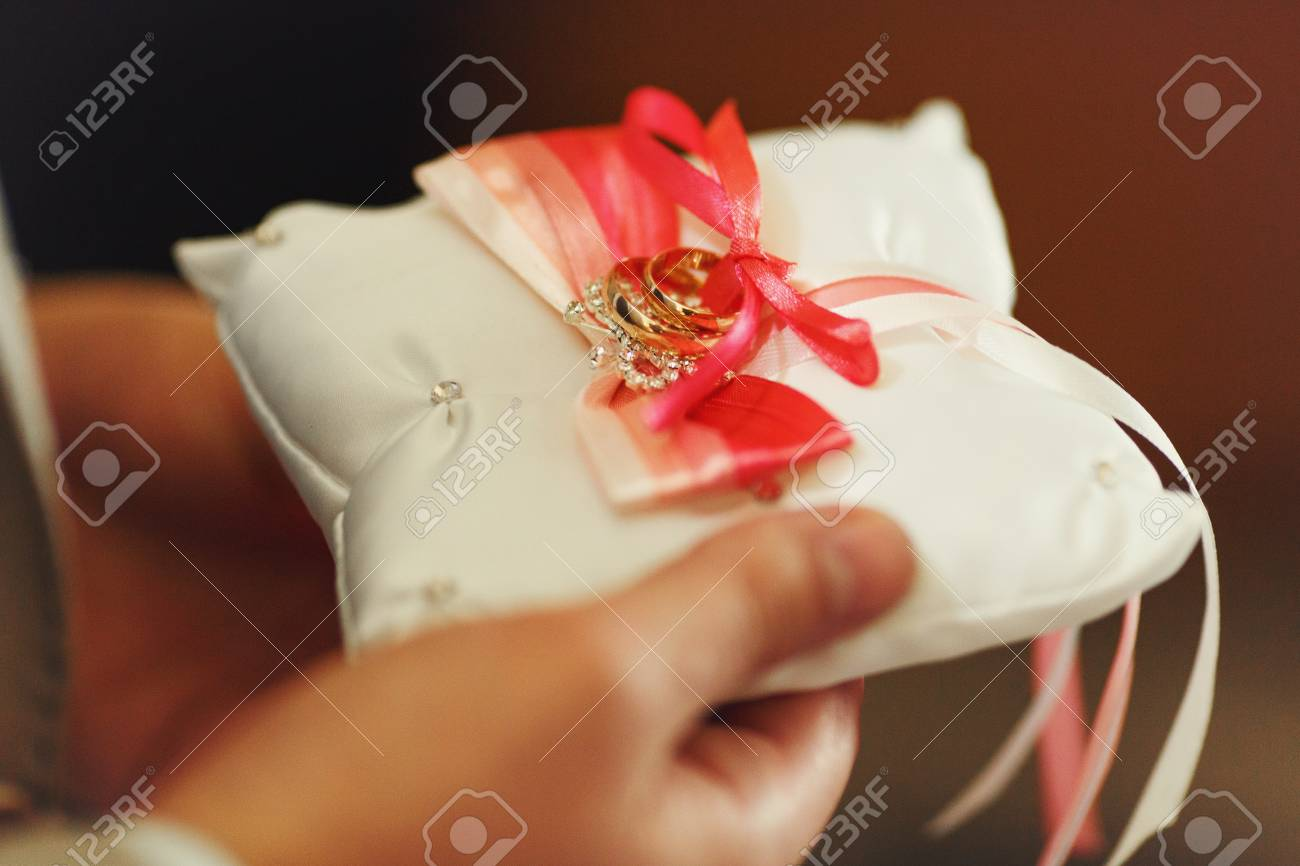 Man Holds A Pillow With Wedding Rings Decorated With Red And Stock