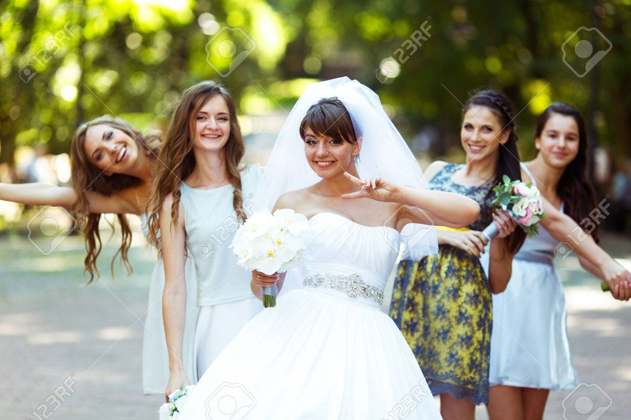 Bride Rises The Sign Of Virctory Posing With Pretty Bridesmaids