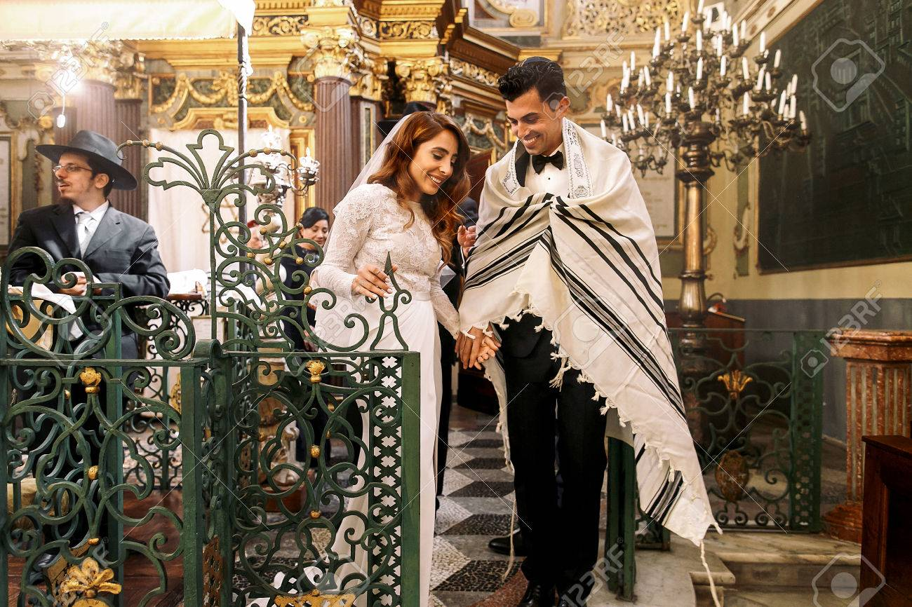 Jewish wedding. Newlyweds walk through the synagogue - 75660956