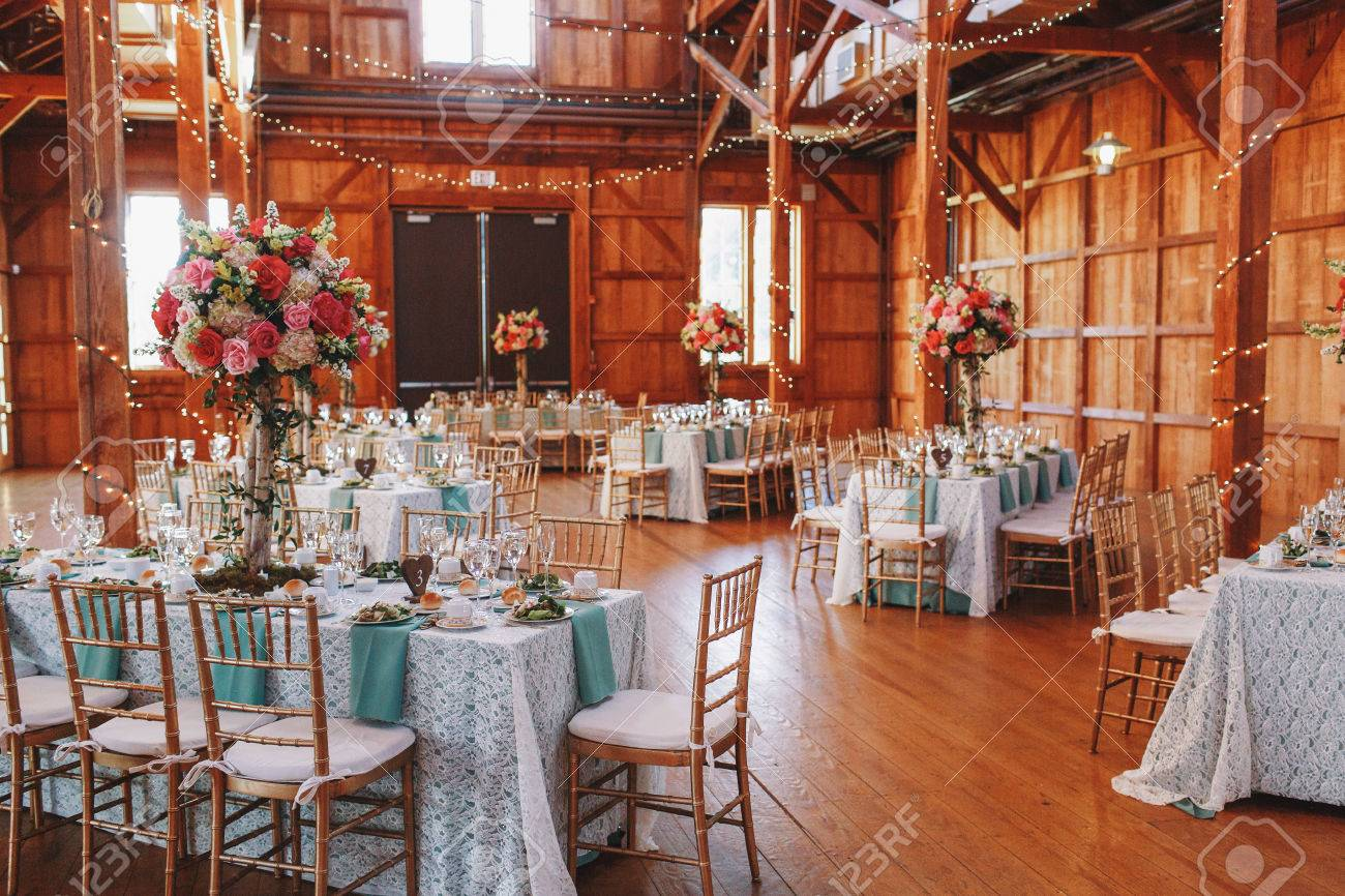 White lace clothes hang from the dinner tables served for wedding party - 78577032