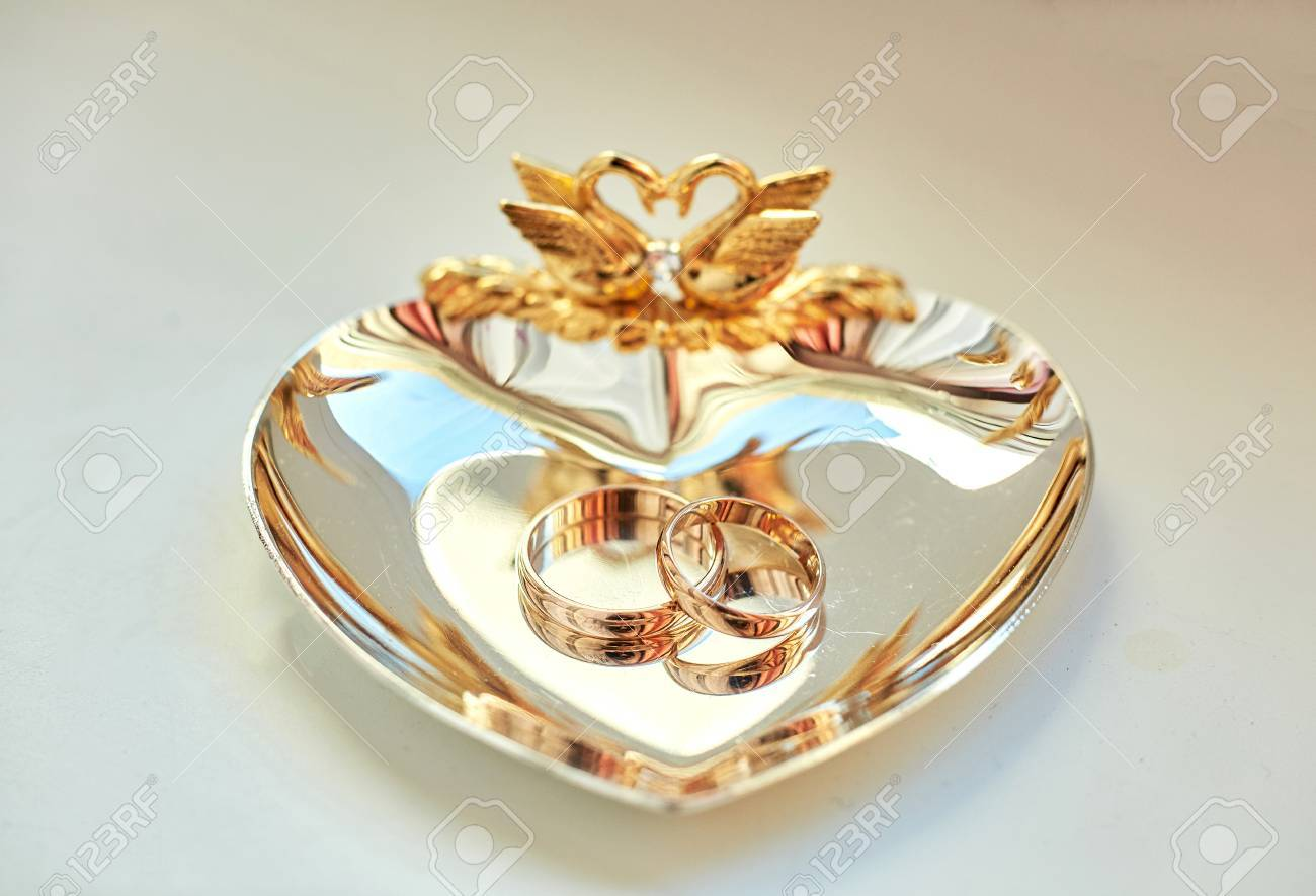 Wedding Rings Lie On The Beautiful Golden Plate Decorated With ...