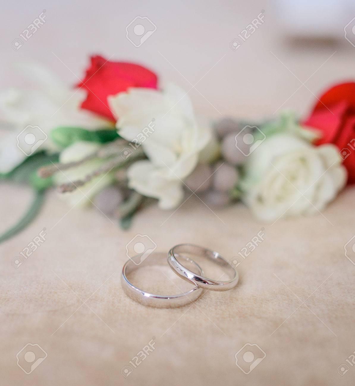 Silberne Hochzeitsringe Liegen Vor Boutonnieres Aus Roten Und Weissen
