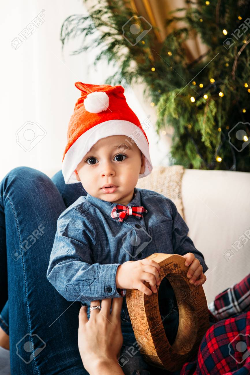 a57f0777c94 Christmas family portrait of happy smiling little boy in red santa hat in  mother s hands.