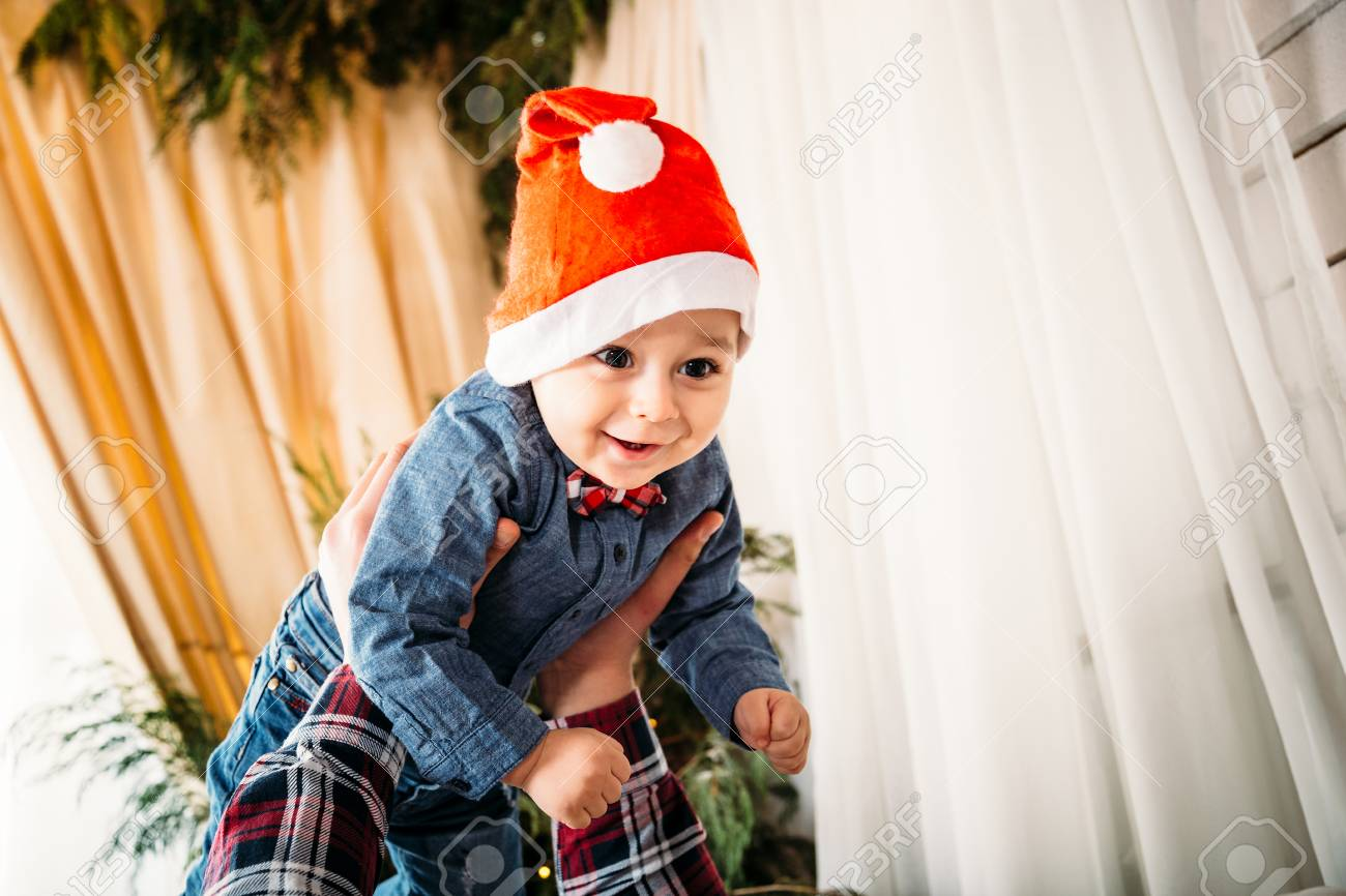 79872e752cb Christmas family portrait of happy smiling little boy in red santa hat in  father s hands.