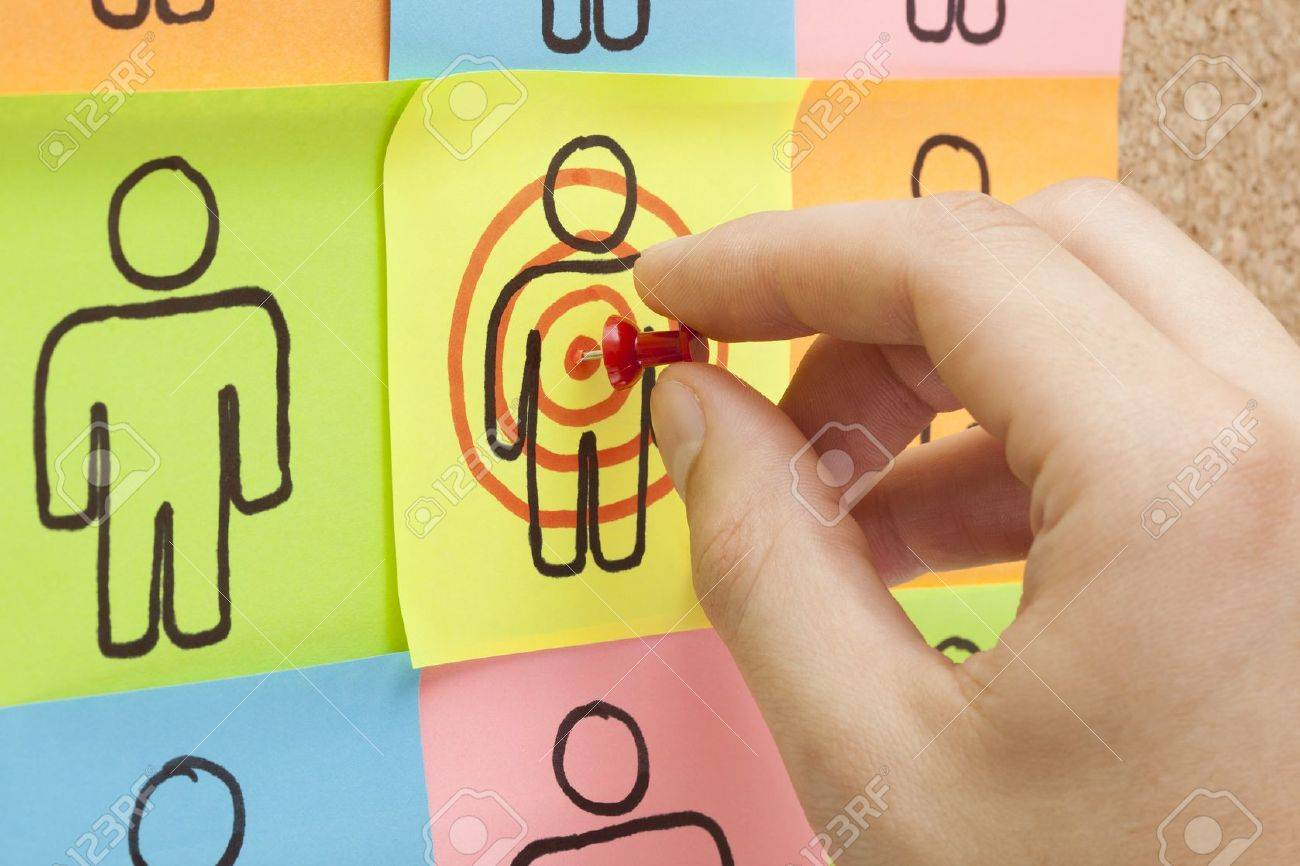 Hand pinning a sticky note in the center of a customer target on cork board Stock Photo - 15113561