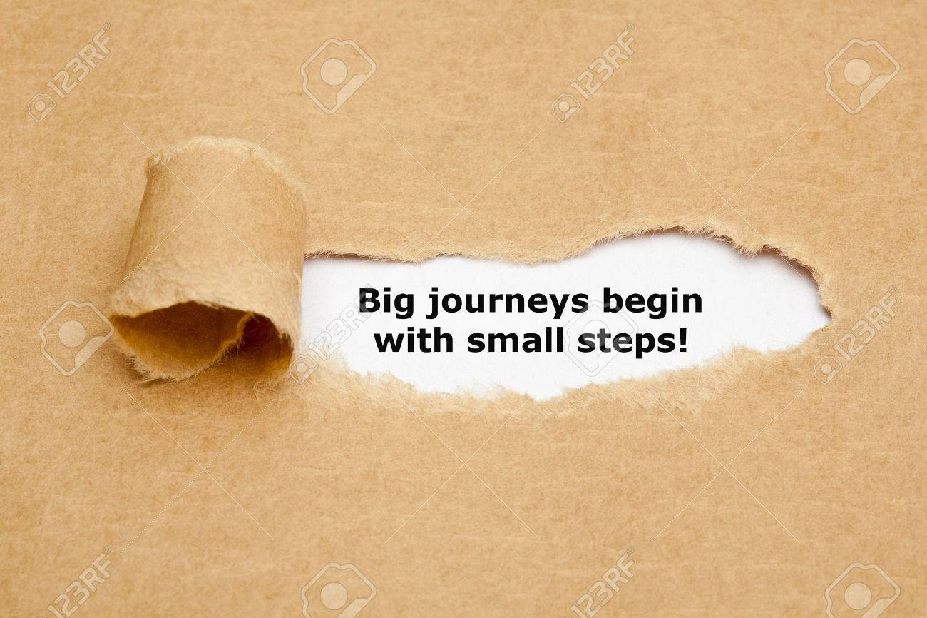The motivational quote Big journeys begin with small steps, appearing behind torn brown paper. - 50888045