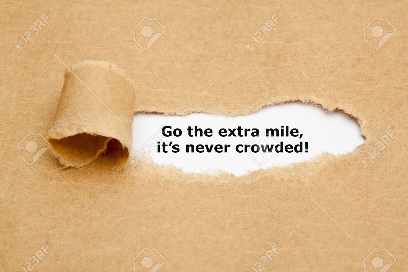 Motivational quote Go The Extra Mile It's Never Crowded appearing behind ripped brown paper. - 68541309