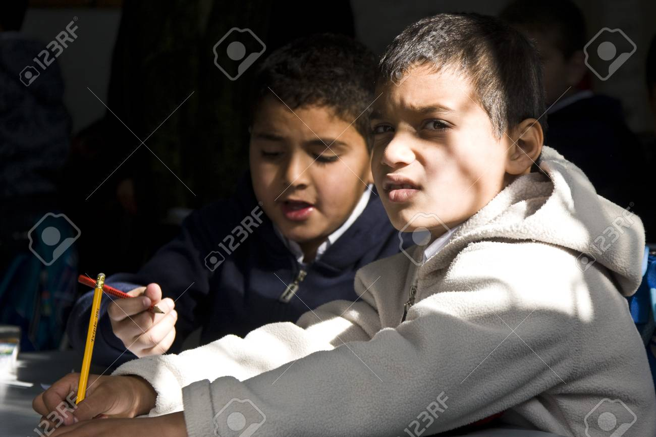 A Muslim kid from a closed school on the Temple Mount in Jerusalem is alerted to see a stranger watching them during the class.Strangers are not allowed in the area except for several hours a day, thus the mere fact of interacting with a stranger is an ou Stock Photo - 10006011
