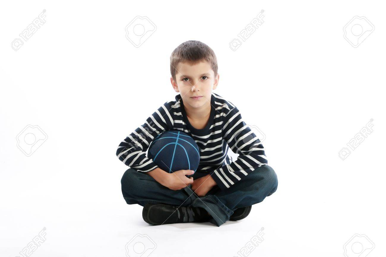 Studio shot of a boy holding the basketball ball while sitting on the floor (isolated on white) Stock Photo - 9974625