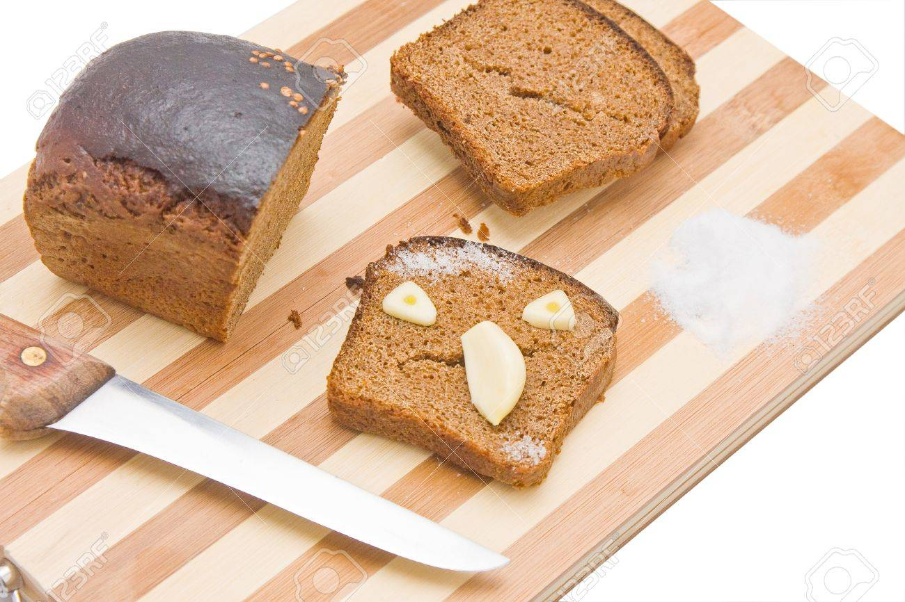 Sliced bread with the chunk and knife on a kitchen board, with a scary face made of bread and garlic Stock Photo - 14360827