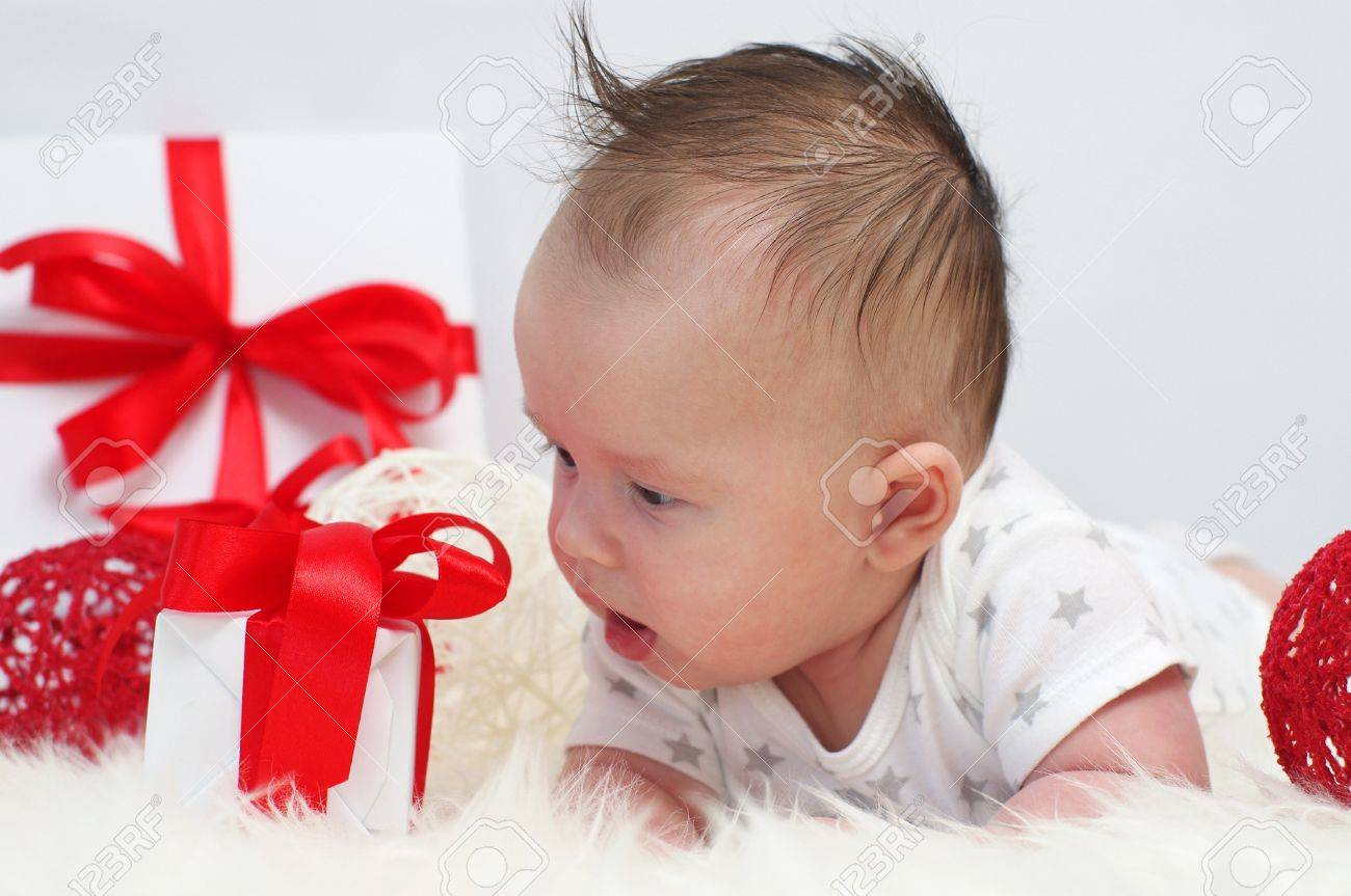 The baby looks at a gift tied up by a red ribbon  3,5 months Stock Photo - 17420828