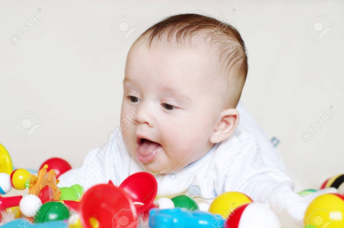 The happy baby lies on a stomach among toys Stock Photo - 17452049