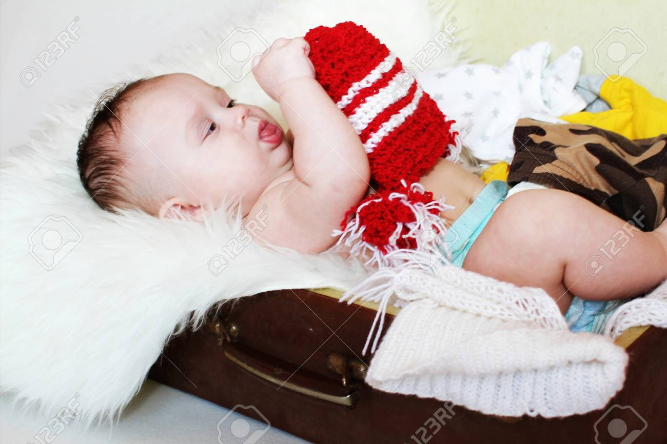 The baby looks at a hat, lying in a suitcase  3,5 months Stock Photo - 17567111