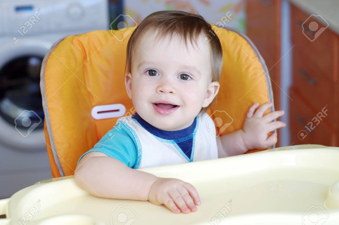 lovely baby boy age of 1 year sitting on baby chair on kitchen