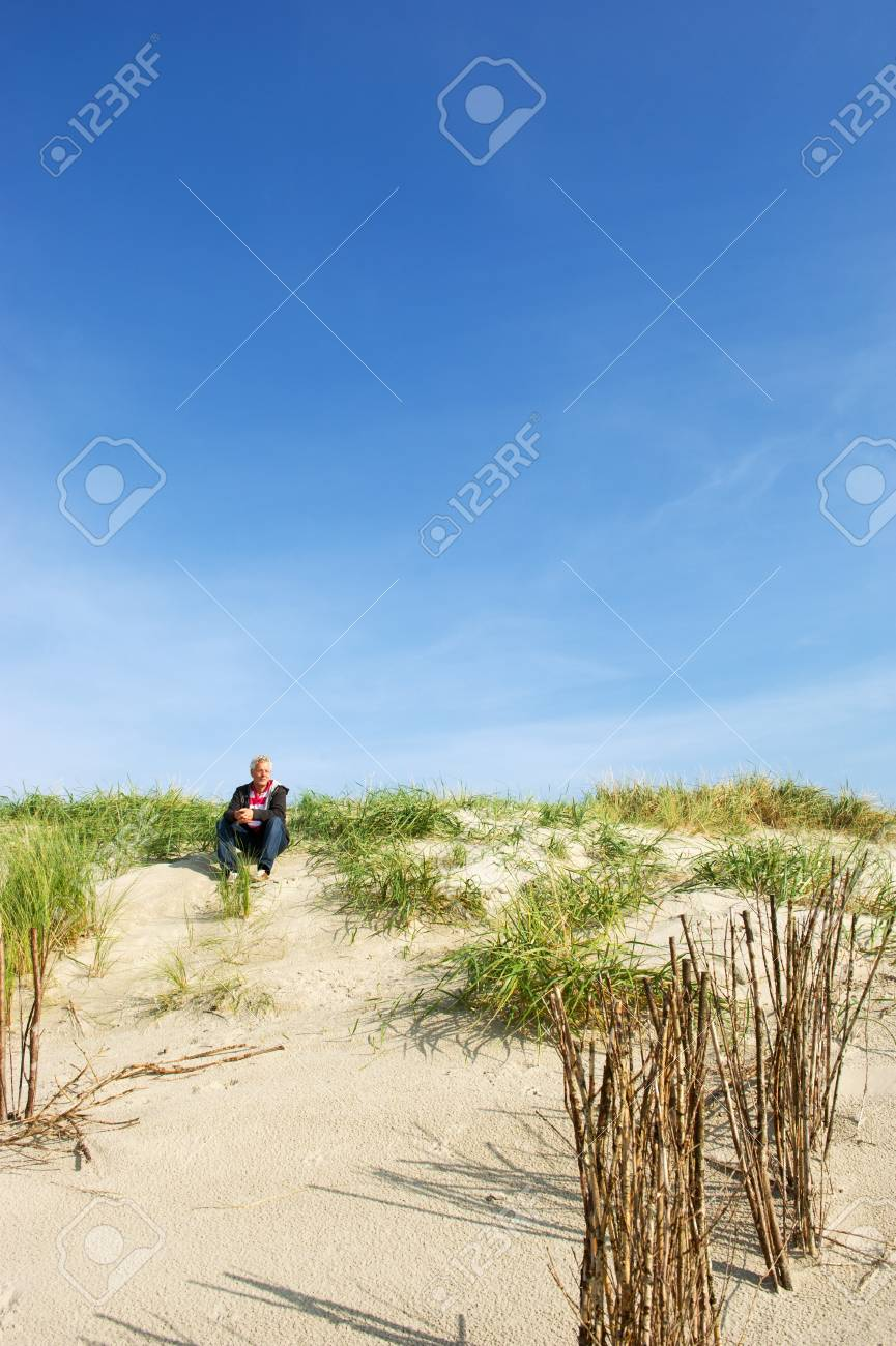 Elderly man is resting in the dunes at the Dutch island Ameland Stock Photo - 9357539