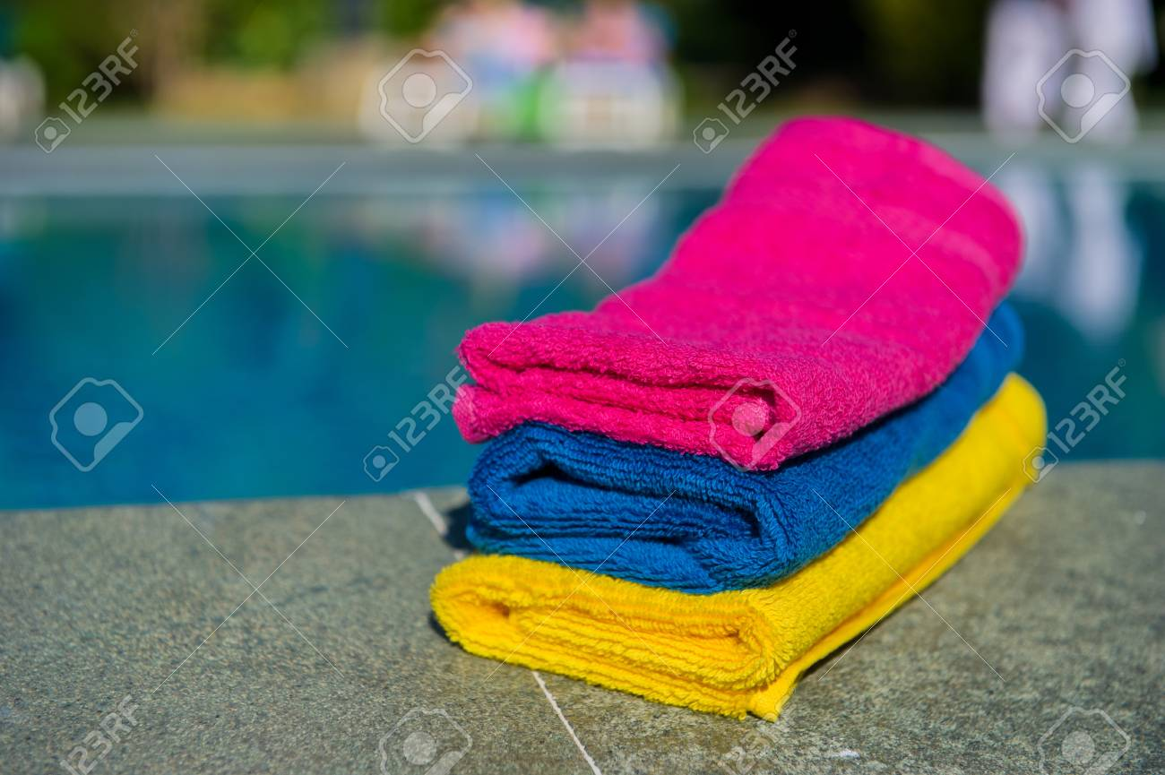 Colorful folded towels near the swimming pool