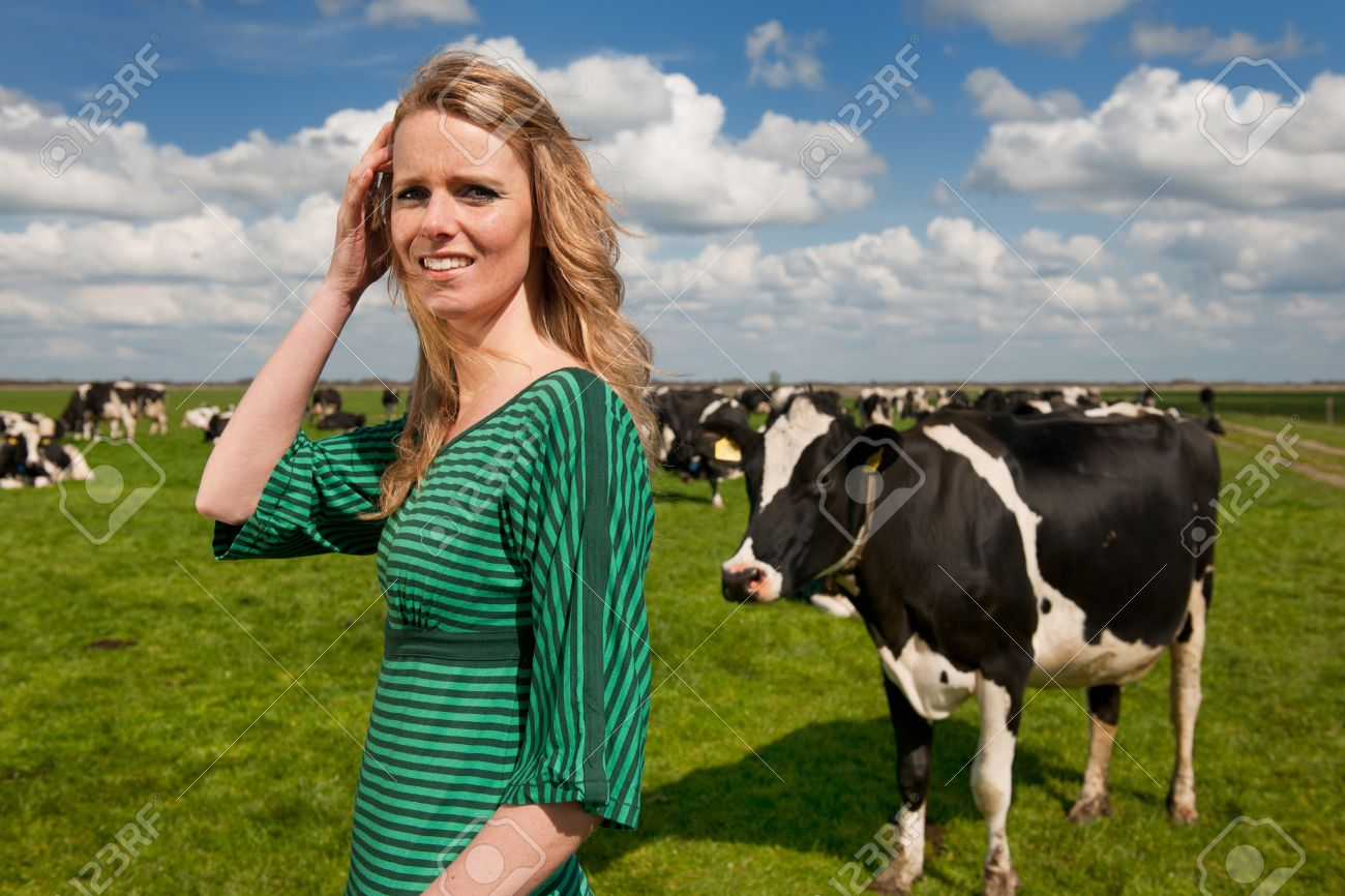 Young blond Dutch girl in farm field with black and white cows Stock Photo - 13712836