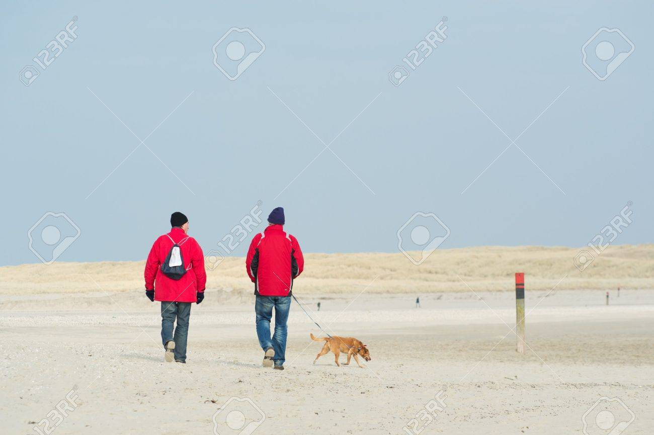 Two man with dog are hiking at the coast Stock Photo - 17893526