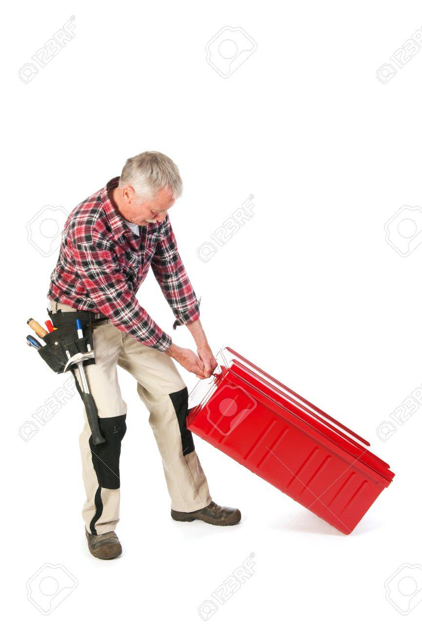 Senior man as manual worker pulling at heavy red tool kit Stock Photo - 21403373
