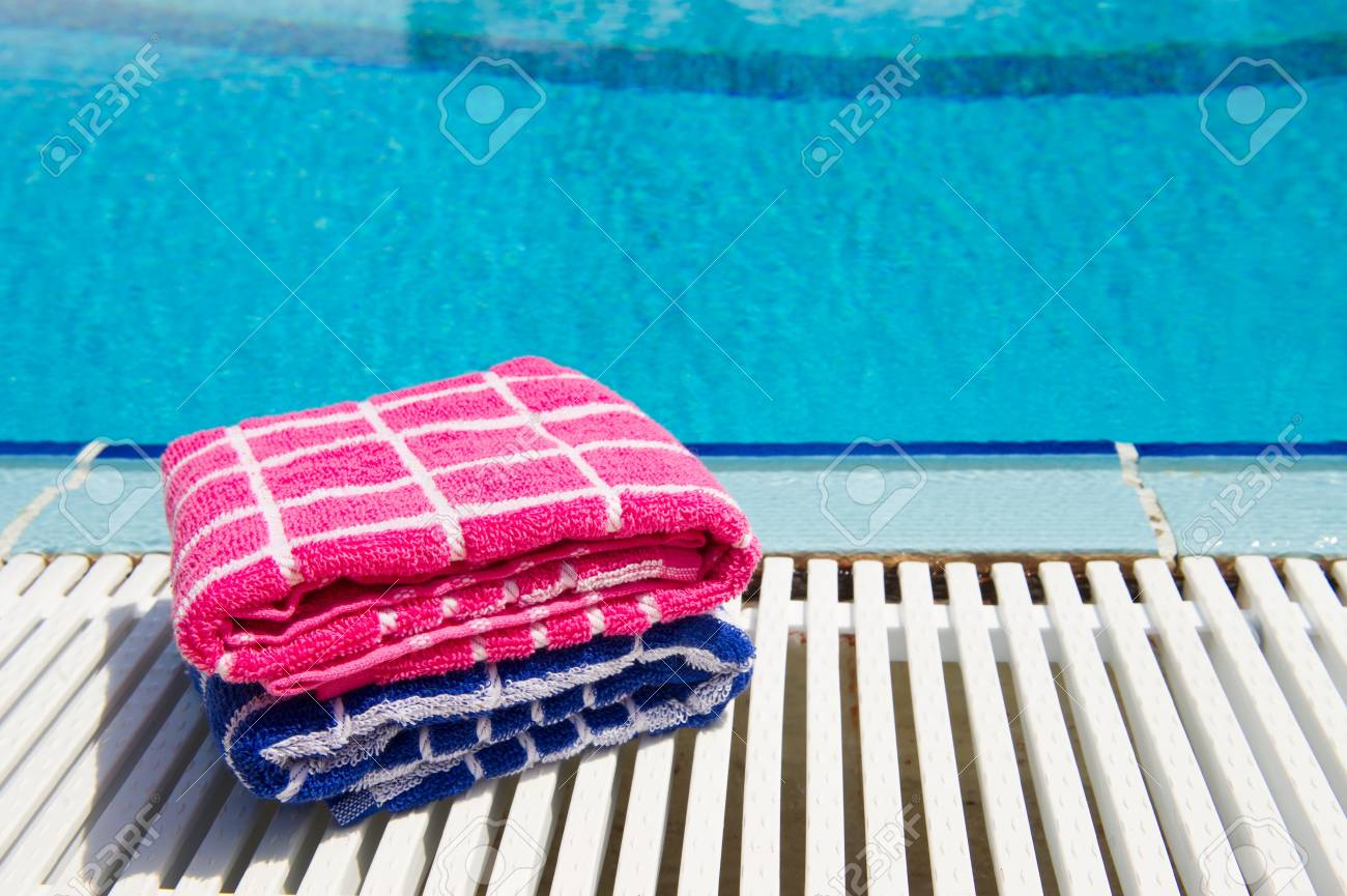 Stacked pink and blue towels at swimming pool