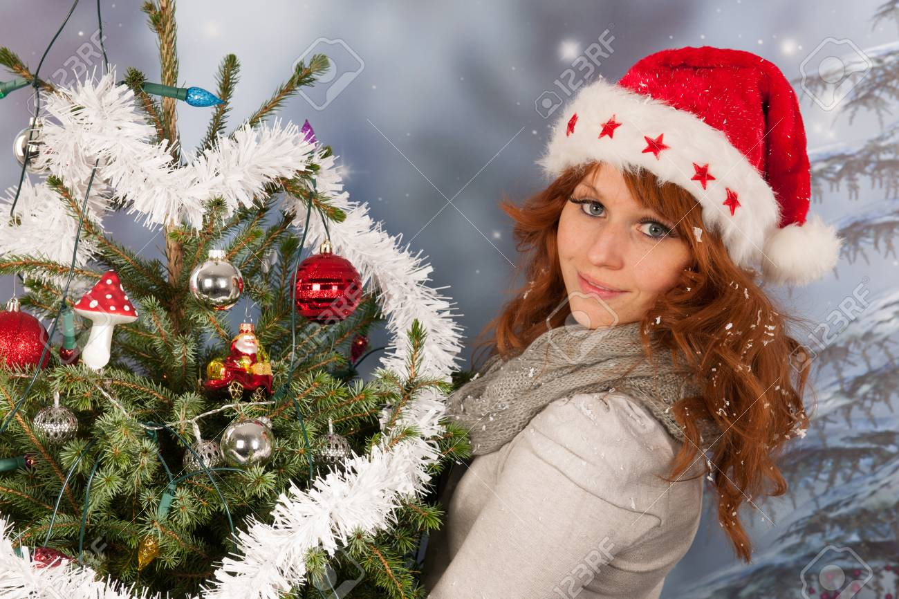ed9dcf3efa4e6 Portrait of woman in winter with snow and hat Santa Claus and Christmas  tree Stock Photo