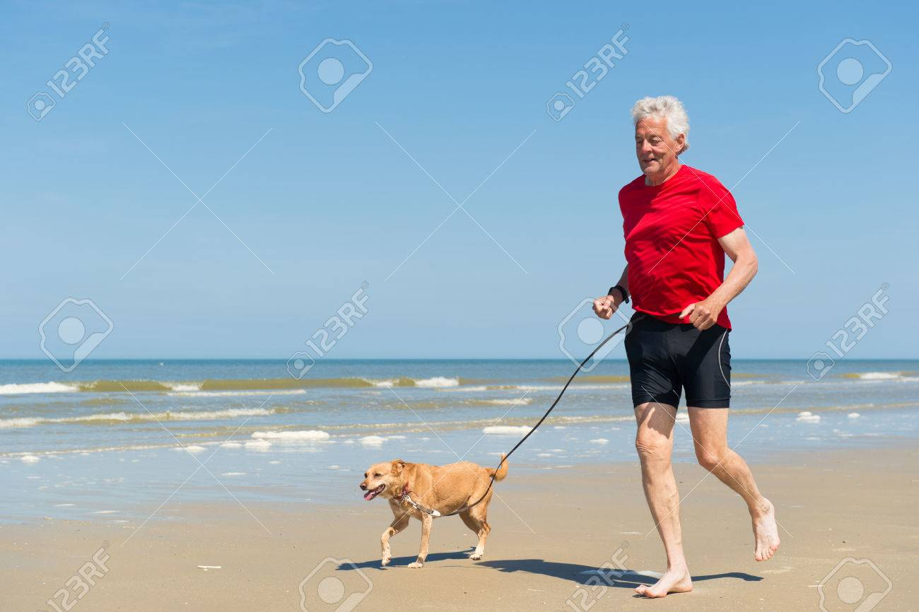 Senior runner with dog at the beach - 36289758