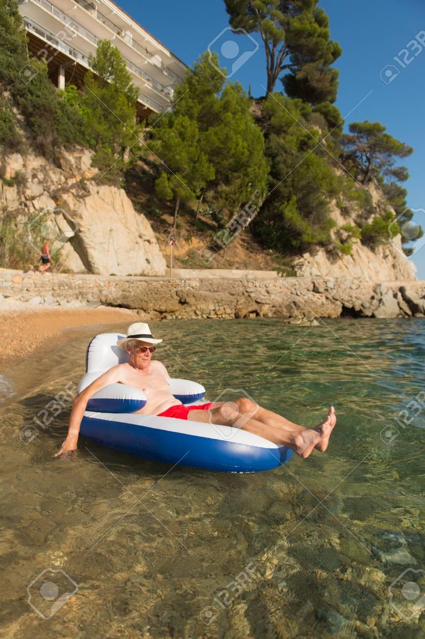Lterer Mann Im Urlaub Der Auf Stuhl Im Meer Schwimmt Lizenzfreie